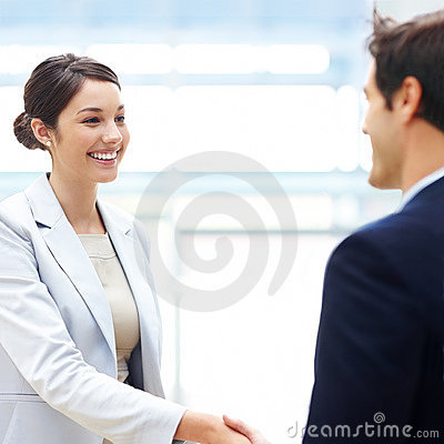 Female executive shaking hands with her coworker