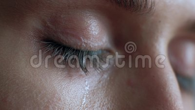 The female eye cries and tears are flowing macro video. Close-up woman eye cries and tears flow. 4k. Macro shoot stock video