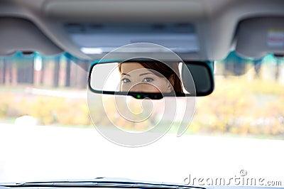Female eyes in salon a car mirror