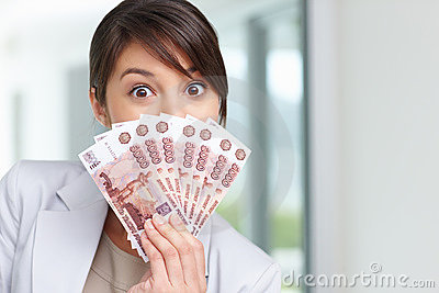 Female with a fan of currency notes over her face