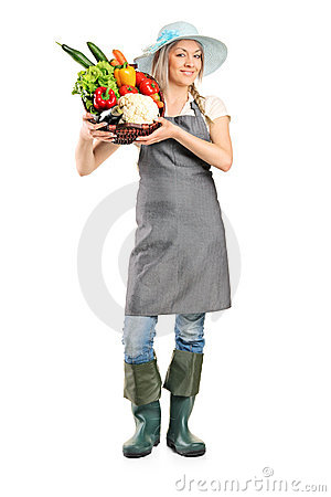 Female farmer holding a basket full of vegetables