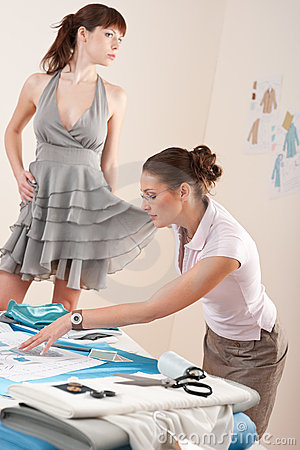 Female fashion designer trying dress on model