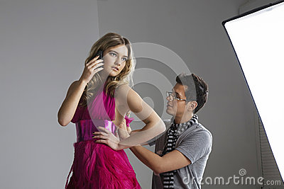Female fashion model using cell phone while designer adjusting her dress in studio