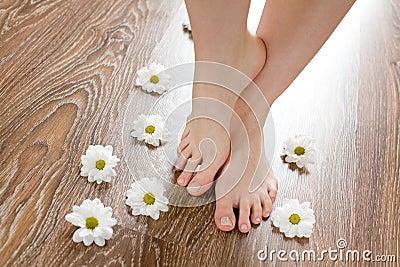 Female feet on the dark floorboard