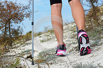 Female feet and trekking stick