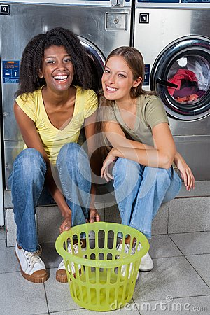 Female Friends Sitting Together Against Washing