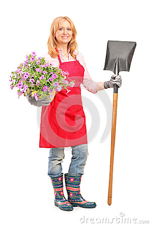 Female gardener holding a shovel and flowers