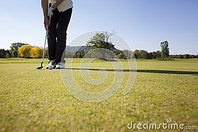 Female golf player putting ball.