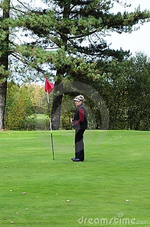 Female golfer standing next to putting flag