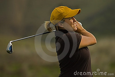 Female golfer swinging iron club