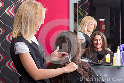 Female hairdresser makes hairstyle for beautiful girl