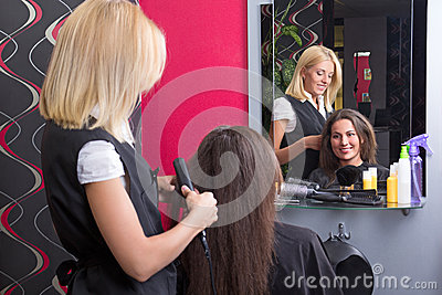 Female hairdresser straightening woman s hair in beauty salon