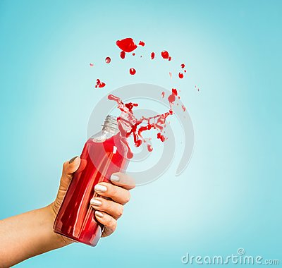 Free Female Hand Holding Bottle With Red Splash Summer Beverage: Smoothie Or Juice Stock Photos - 112326133