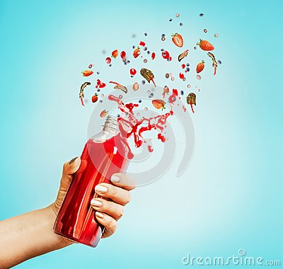 Free Female Hand Holding Bottle With Red Splash Summer Beverage: Smoothie Or Juice And Berries Stock Photography - 112326122