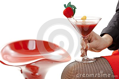Female hand holding cocktail drink in bar isolated