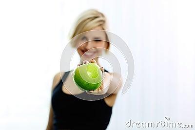 Female hand holding green apple