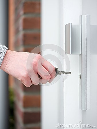 Free Female Hand Holding Key To Insert In Door Lock Stock Image - 44634621
