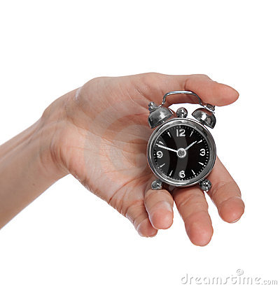 Female hand holding a small alarm clock. Female Hand Holding A Small Alarm Clock Stock Photography   Image