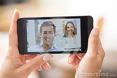 Female hand holding a smartphone during a skype video