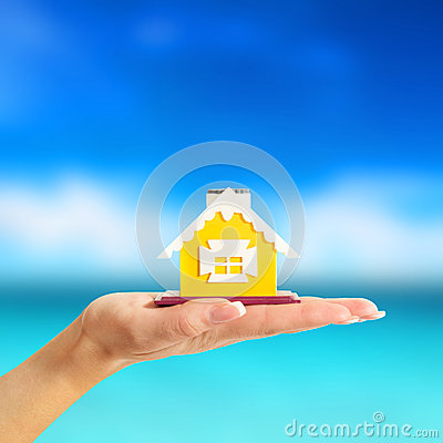 Female hand holding a yellow house on sea background