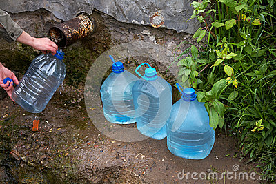 The female hand holds plastic bottle with water