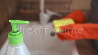 A female hand in an orange glove puts detergent on a sponge, rinses the plate on the kitchen sink - does household stock footage