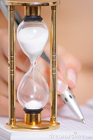 Female hand with pen and sand clock