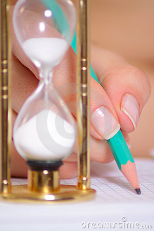 Female hand with a pencil and a sand clock
