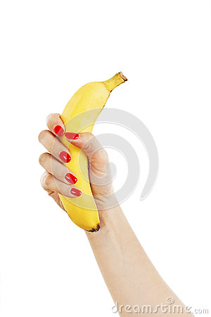 Female hand with red nails holding a banana