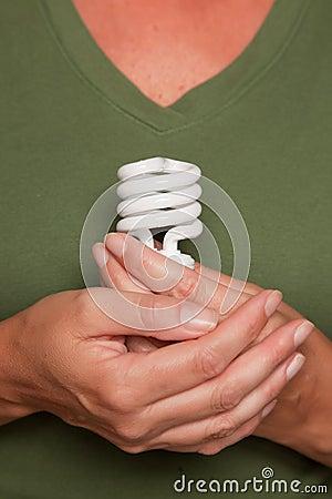 Female Hands Holding Energy Saving Light Bulb