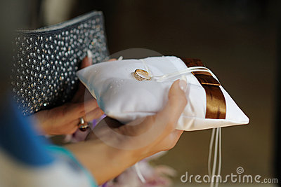 Female hands holding pillow with wedding ring