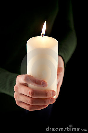 Female hands holding a white candle, shallow DOF