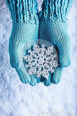 Free Female Hands In Light Teal Knitted Mittens With Sparkling Wonderful Snowflake On A White Snow Background. Winter Christmas Concept Royalty Free Stock Photo - 61553305