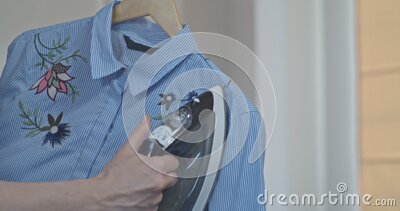 Female hands are ironing clothes that hangs on the railing, steams in vertical situation, a professional iron with steam stock video footage
