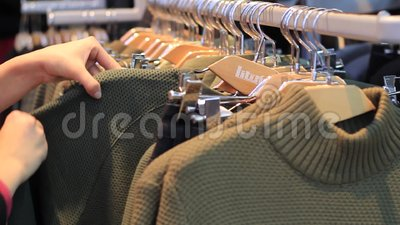 Female hands on touch a coat hanger with clothes in boutique