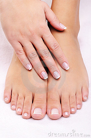 Female hands on the well-groomed feet