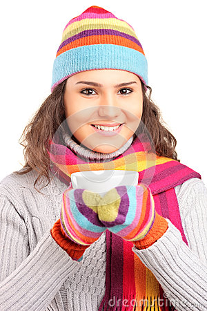 Female with hat and scarf and holding a cup of tea