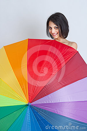 Female hiding over rainbow umbrella