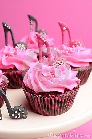 Female high heel stiletto shoes decorated pink and black red velvet cupcakes - close up on pink cupcake.