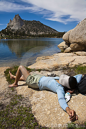 Female hiker relaxing near a lake.