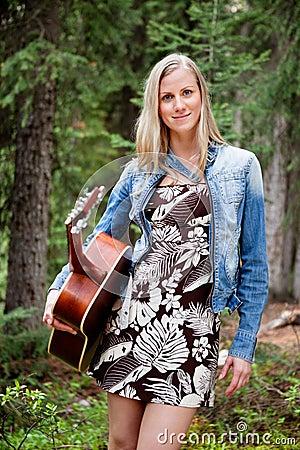 Female holding guitar against trees