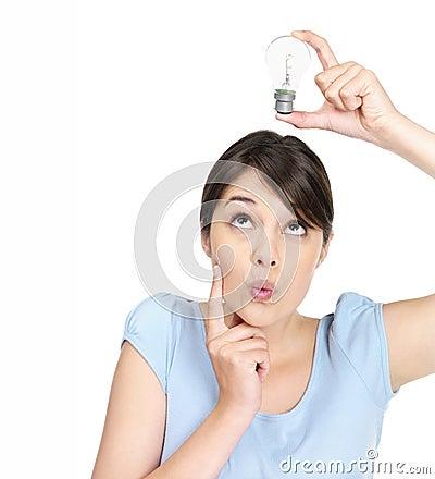 Female holding a light bulb over head on white