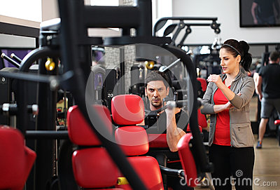 Female instructor explaining to a man how to workout