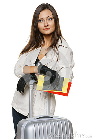 Female in jacket and gloves standing with travel bag
