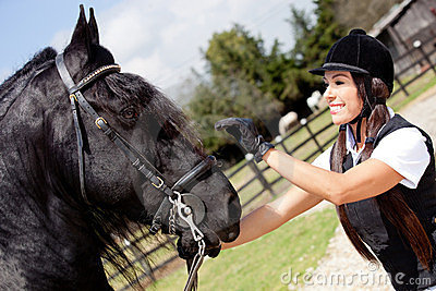 Female jockey stroking a horse