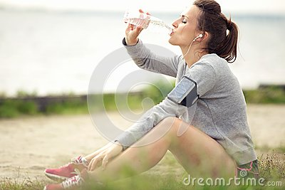 Female Jogger Resting and Drinking Bottled Water