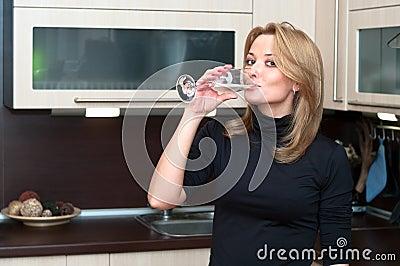 Female in kitchen drinking champagne