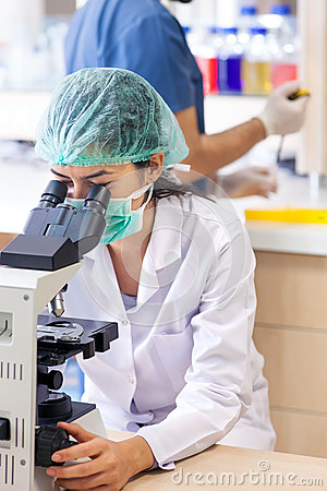 Female lab technician sitting at a microscope.