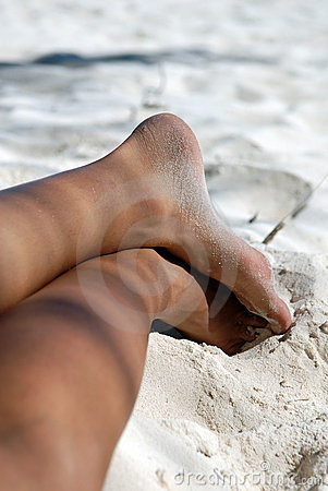 Female legs on beach