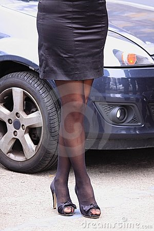Female legs and car in town
